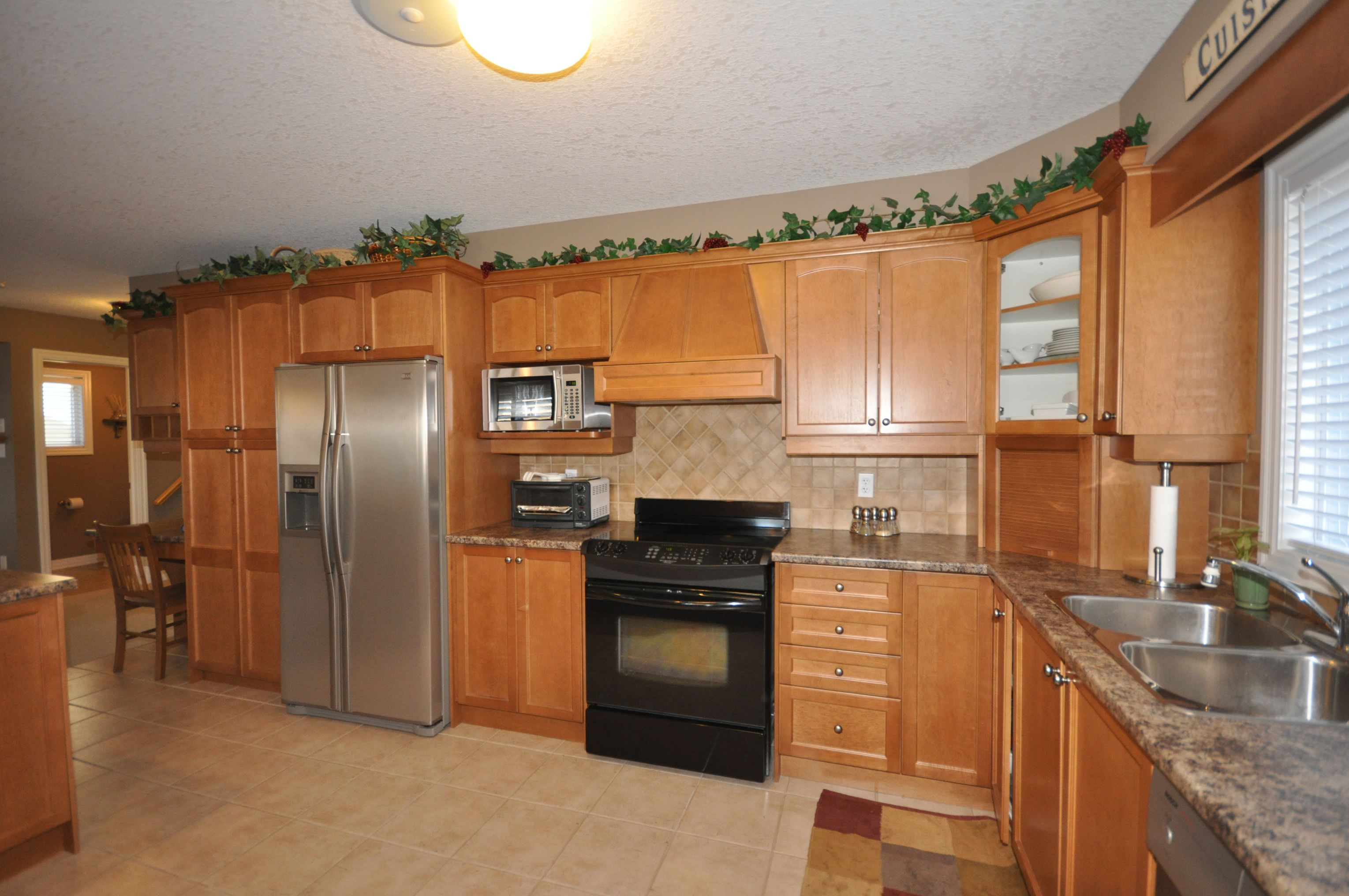 Spacious kitchen has ceramic backsplash & flooring