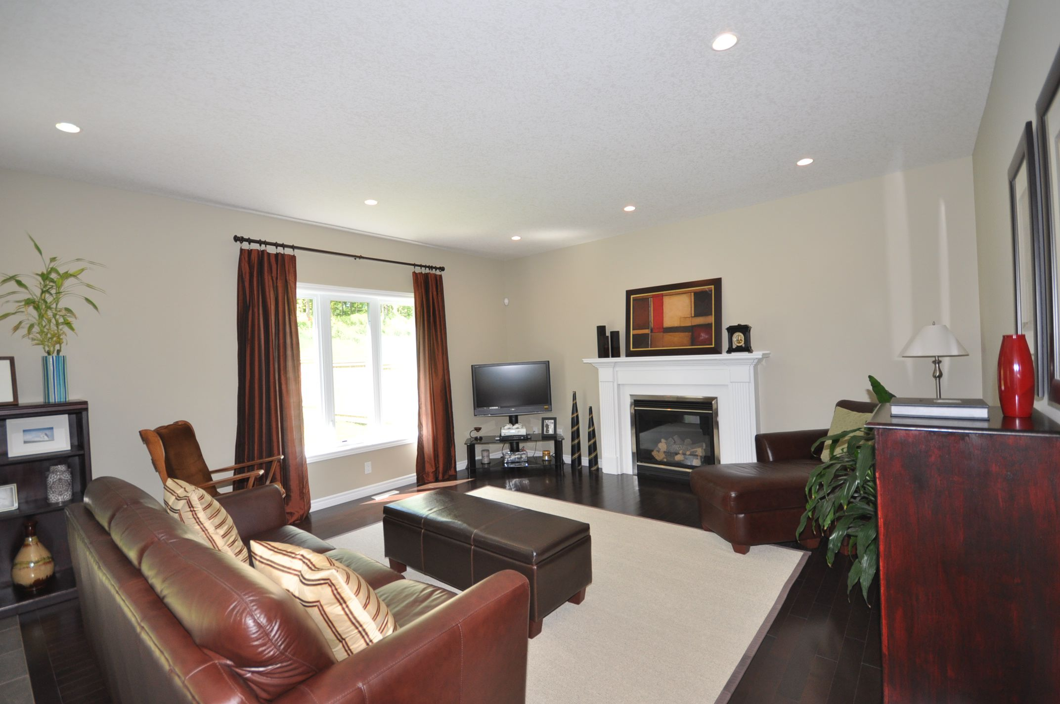 Great Room with large sunny window, cozy gas fireplace & hardwood floors