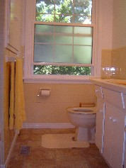 Bright sunny bathroom with new flooring and a handy linen closet