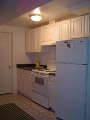 The lower level also has a full kitchen with white cabinetry and 3 piece bath