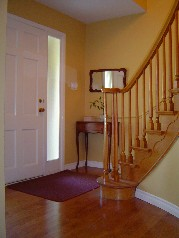 Spacious foyer has newer wide plank hardwood flooring & circular stairage to 2nd floor