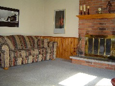 The family room has a cozy fireplace, beamed ceiling and a patio door to a 4 seasons room
