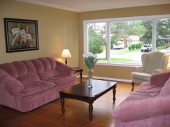 The large sunny living room has warm hardwood flooring & like the remaider of the house,its freshly painted