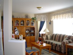 The main floor family room with large sunny bay window is open to the kitchen