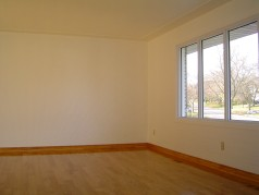 Huge living room with large sunny window and gleaming new hardwood floors