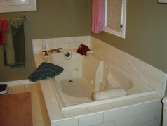 The ensuite enjoys a deep whirlpool tub and ceramic flooring.