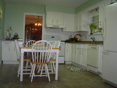 Eat in kitchen with lots of cupboards, a newer floor, counter tops, taps and ceramic backsplash.