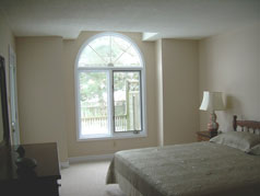 Master bedroom with large window and door to sundeck