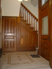 Formal front foyer with decorative ceramic flooring and natural woodwork