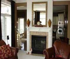 Family room shares double sided gas fireplace with kitchen